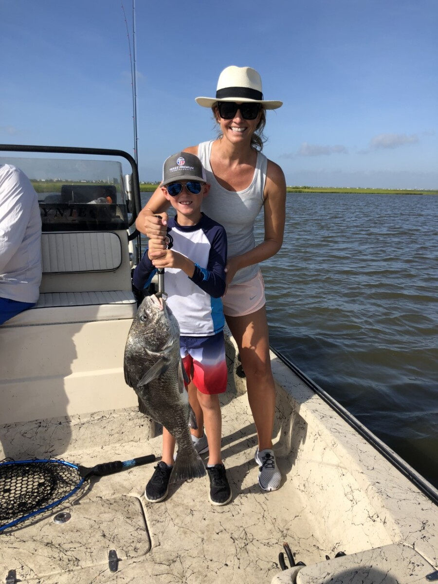 fishing in galveston | Galveston Travel Guide by popular Houston travel blog, Haute and Humid: image of a mom and her son holding a large silver fish on a boat in Galveston Texas.