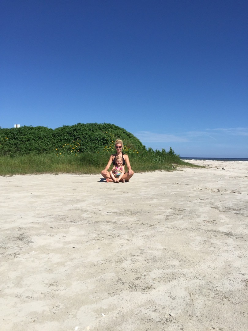 galveston beaches | Galveston Travel Guide by popular Houston travel blog, Haute and Humid: image of a woman and her daughter sitting on a sandy beach in Galveston, Texas.
