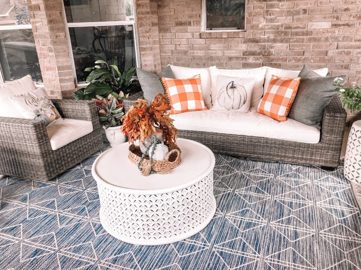 "fall patio decor | Fall Decor by popular Houston life and style blog, Haute and Humid: image of a back patio decorated with a Pottery Barn Torrey All-Weather Wicker Square Arm 86"" Sofa, Pottery Barn Torrey All-Weather Wicker Square Arm Swivel Lounge Chair, West Elm Reflected Diamonds Indoor/Outdoor Rug, Wayfair Lorraine Solid Wood Drum Coffee Table, Amazon MIULEE Set of 2 Retro Farmhouse Buffalo Plaid Check Pillow Cases, Amazon PSDWETS Autumn Decorations Pumpkin Pillow Covers, and Etsy Trellis Grey (Dark) Wooden Bead Garland."