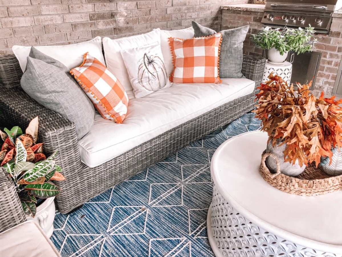 "bargain fall decor | Fall Decor by popular Houston life and style blog, Haute and Humid: image of a back patio decorated with a Pottery Barn Torrey All-Weather Wicker Square Arm 86"" Sofa, Pottery Barn Torrey All-Weather Wicker Square Arm Swivel Lounge Chair, West Elm Reflected Diamonds Indoor/Outdoor Rug, Wayfair Lorraine Solid Wood Drum Coffee Table, Amazon MIULEE Set of 2 Retro Farmhouse Buffalo Plaid Check Pillow Cases, Amazon PSDWETS Autumn Decorations Pumpkin Pillow Covers, and Etsy Trellis Grey (Dark) Wooden Bead Garland."