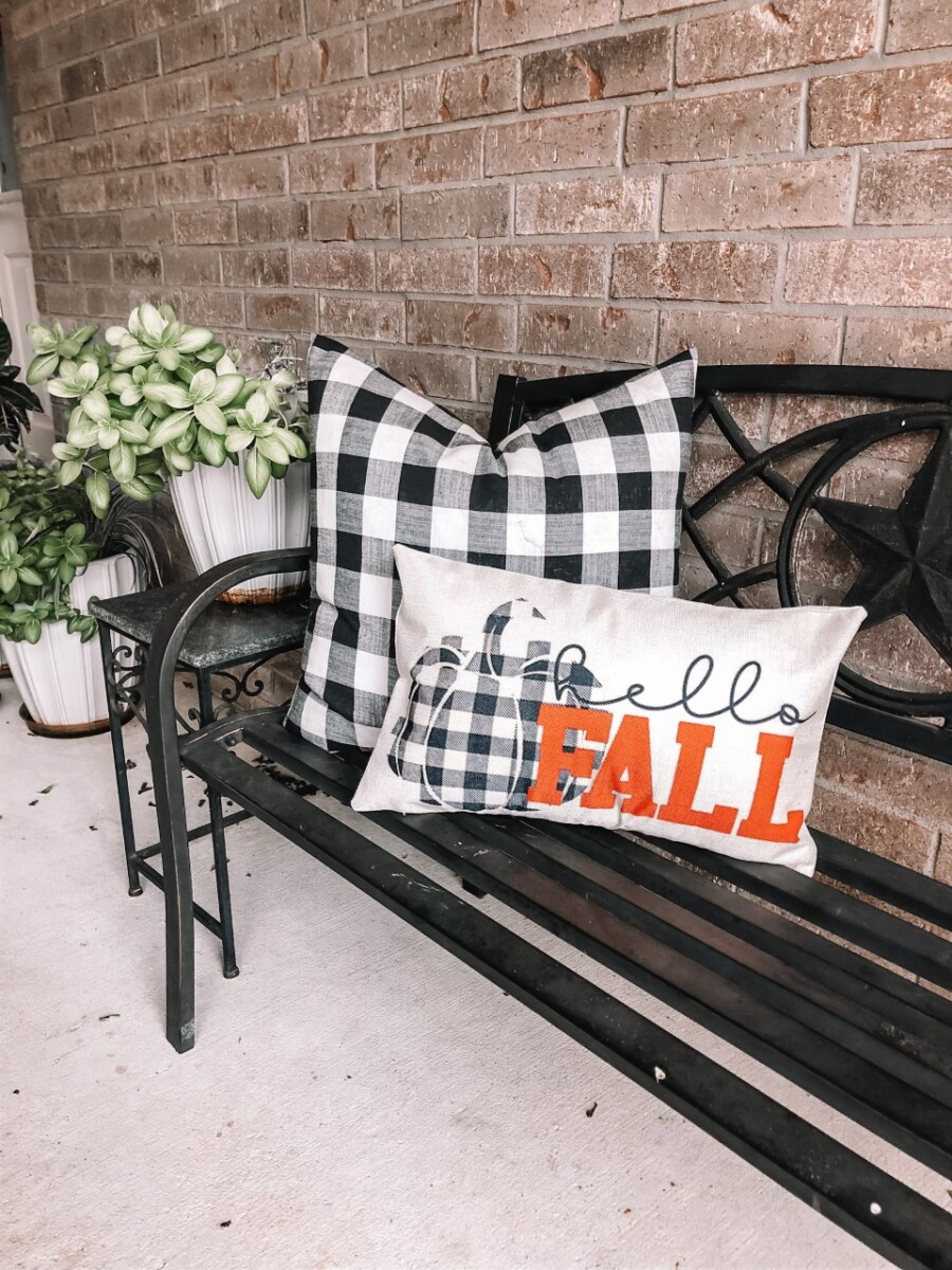 fall pillows | Fall Decor by popular Houston life and style blog, Haute and Humid: image of a black bench with a black and white buffalo check pillow and Hello Fall pillow.