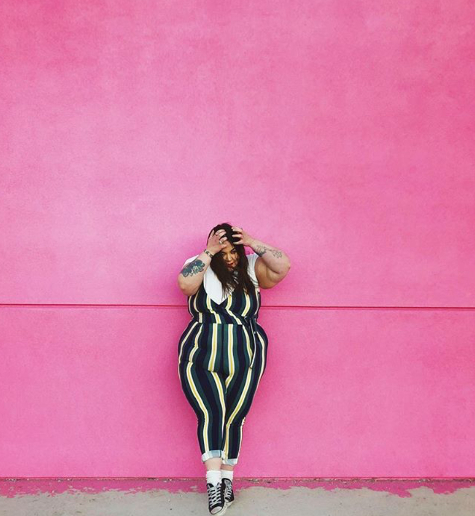 plus size girl in front of hot pink wall