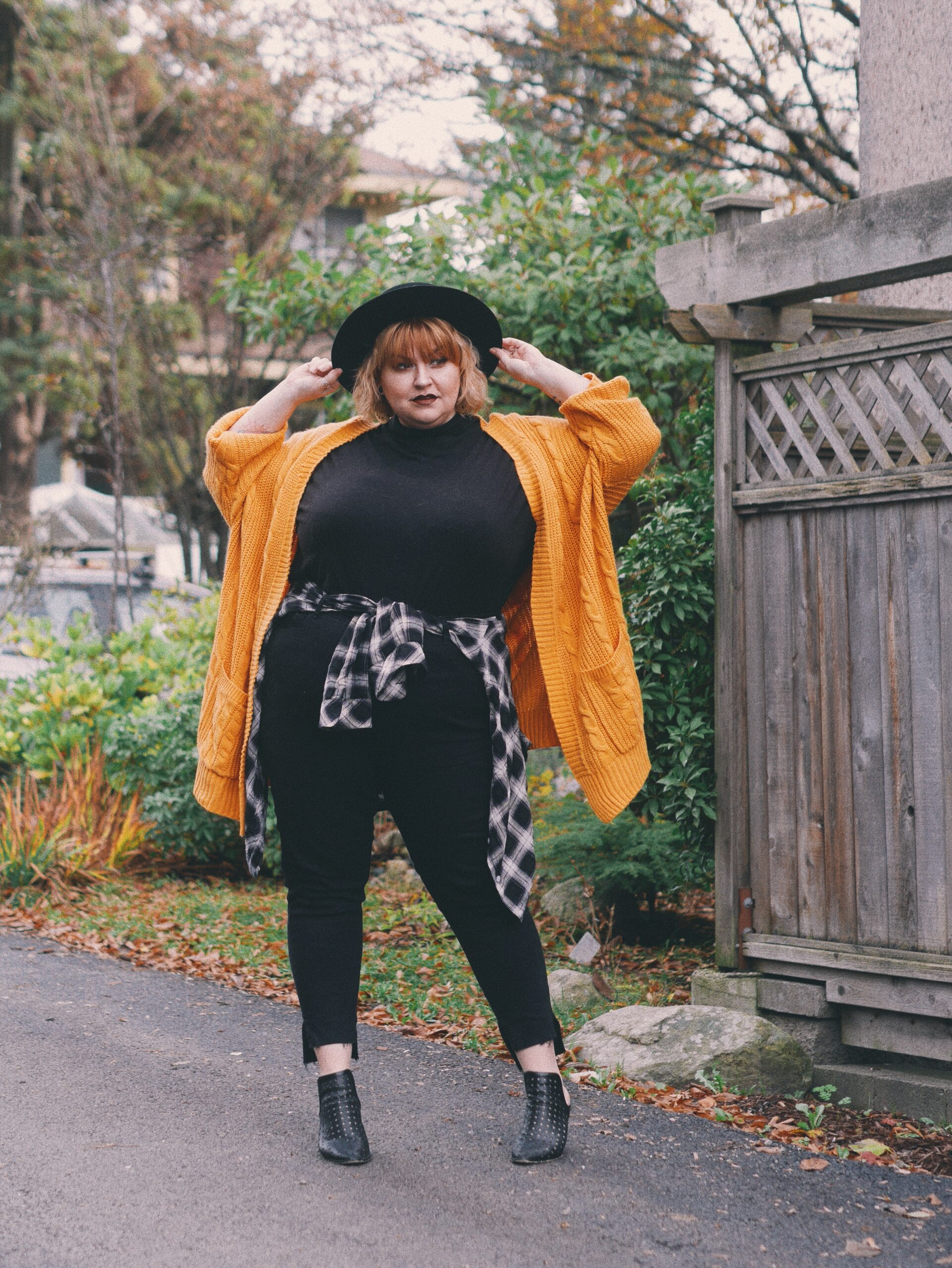 Margot Meanie poses in plus size outfit featuring a yellow sweater and black outfit