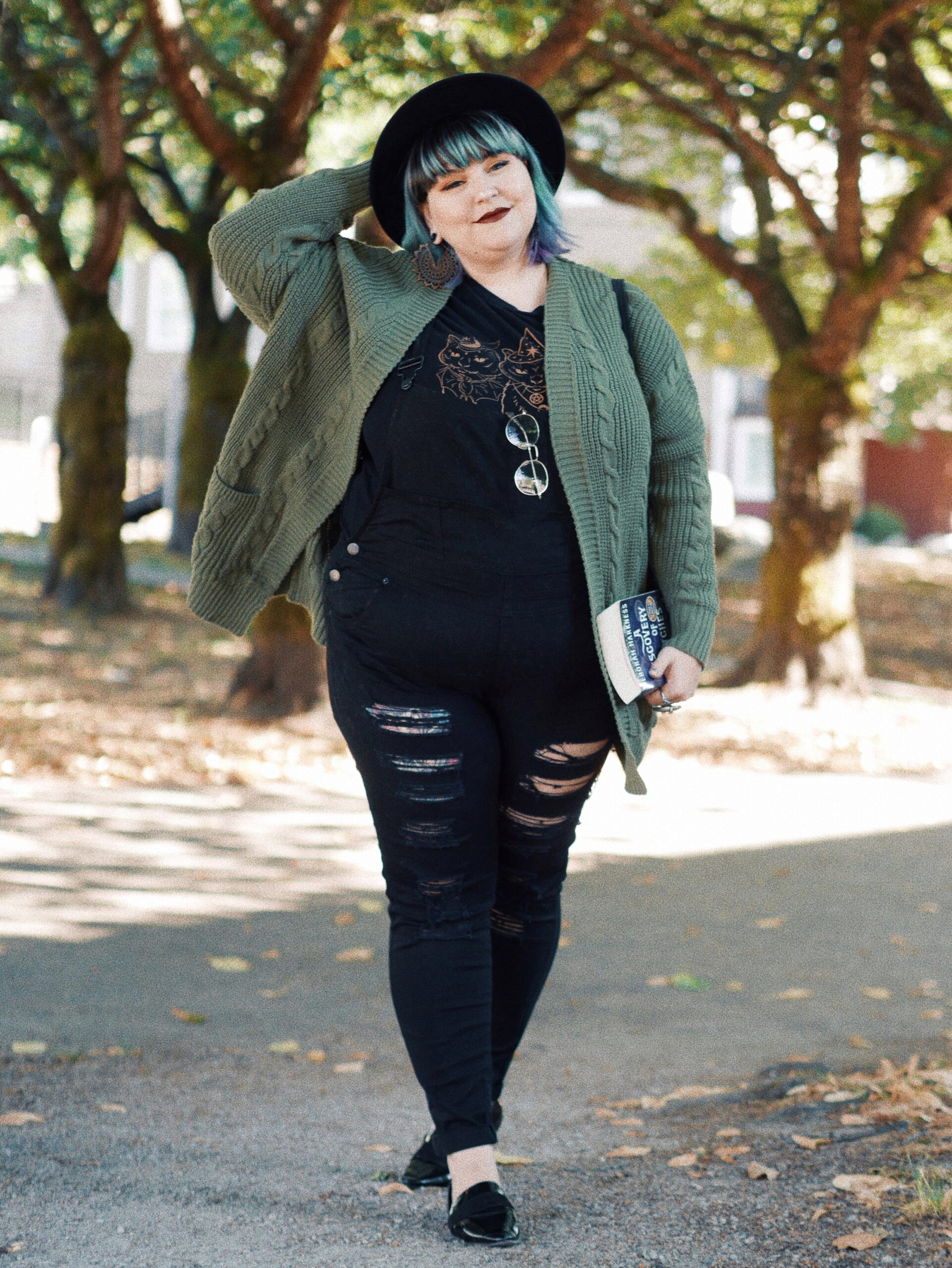Margot Meanie poses in plus size outfit featuring a green sweater and black ripped overalls
