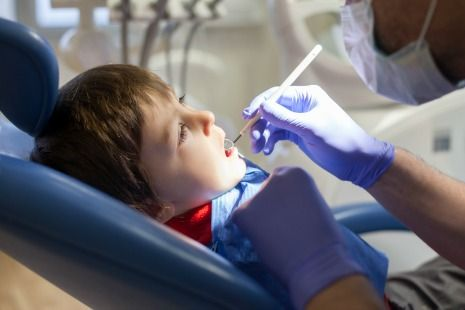 Dentist checking kids teeth
