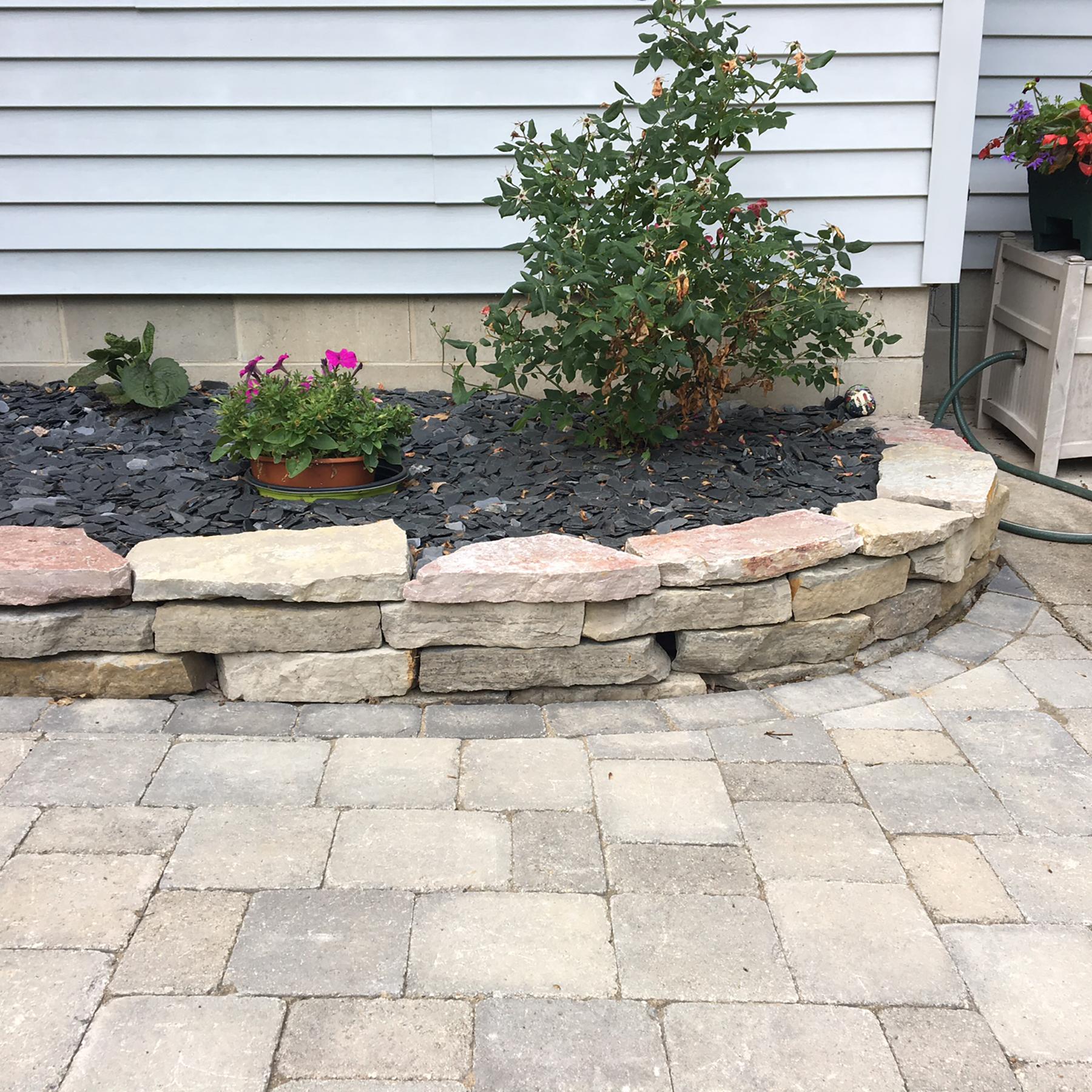 Brick pavers with natural stone retaining wall