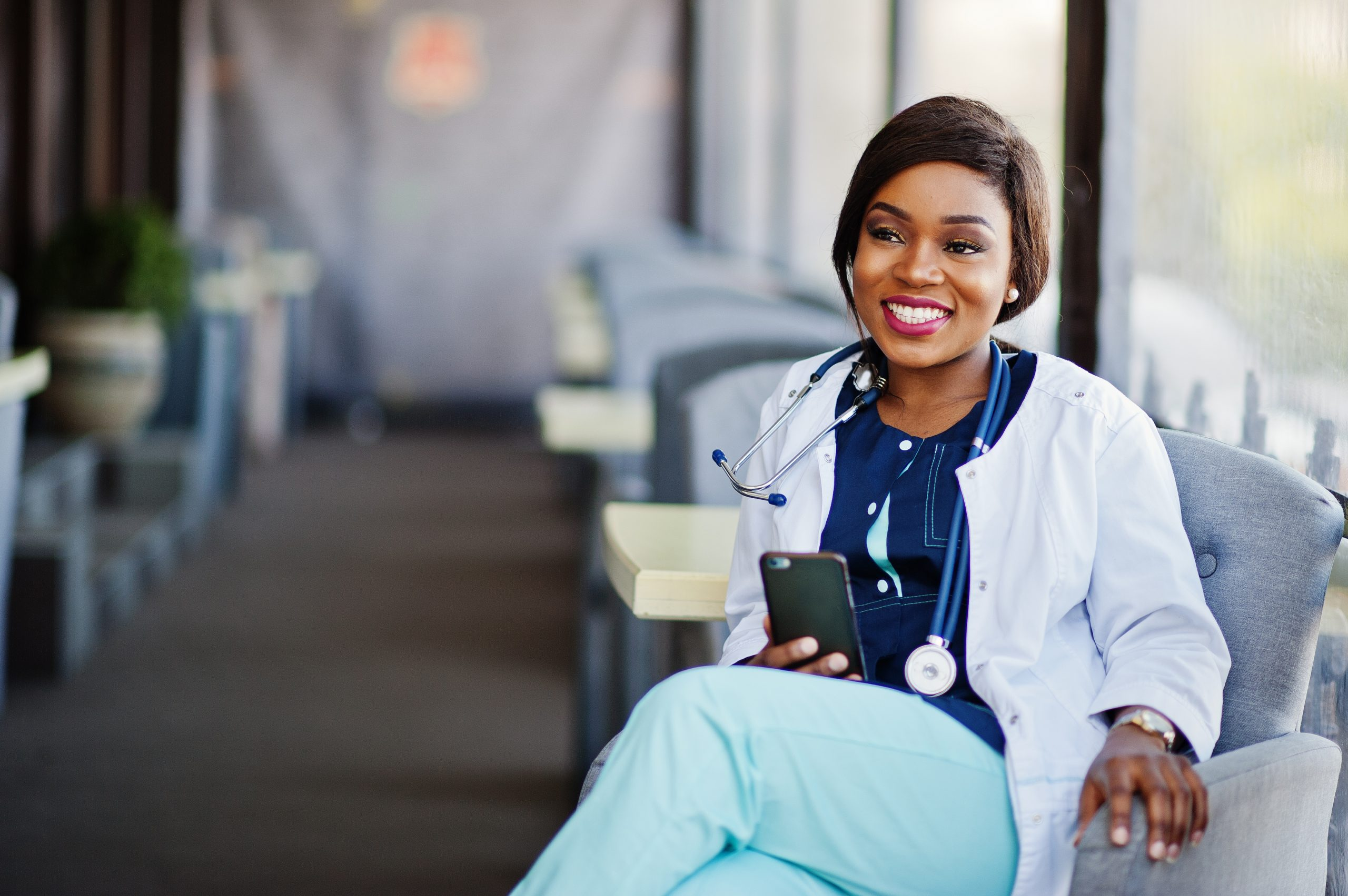 African american doctor female with stethoscope looked at phone and sitting on clinic.