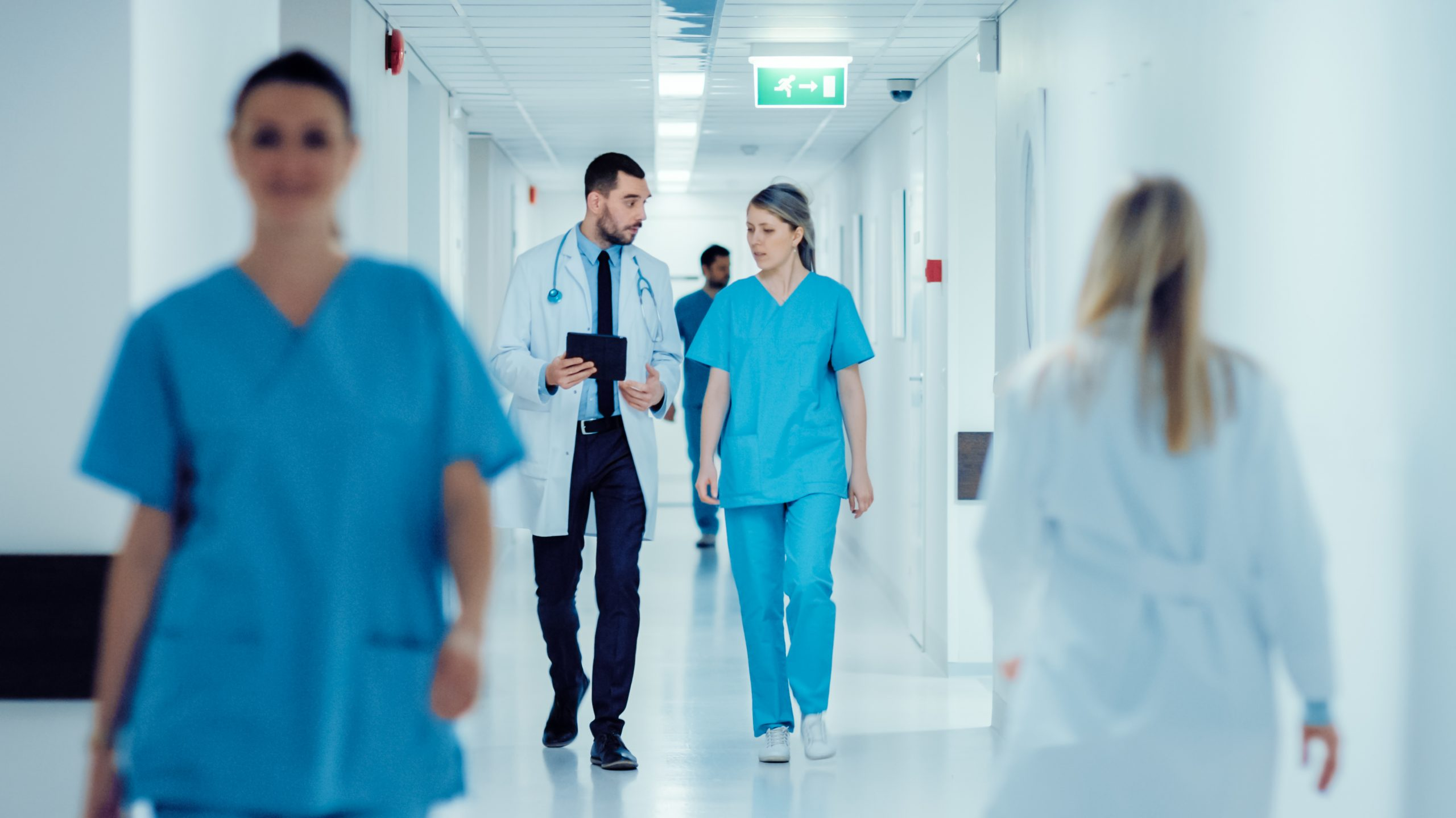 Surgeon and Female Doctor Walk Through Hospital Hallway, They Consult Digital Tablet Computer while Talking about Patient's Health. Modern Bright Hospital with Professional Staff.