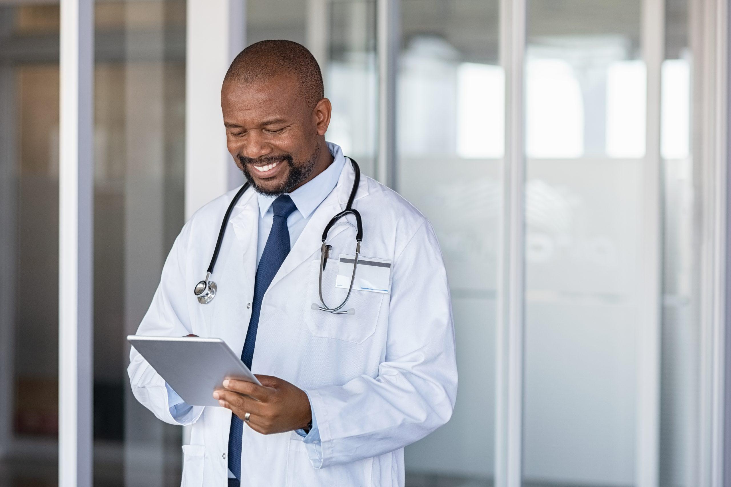 African doctor using digital tablet at hospital