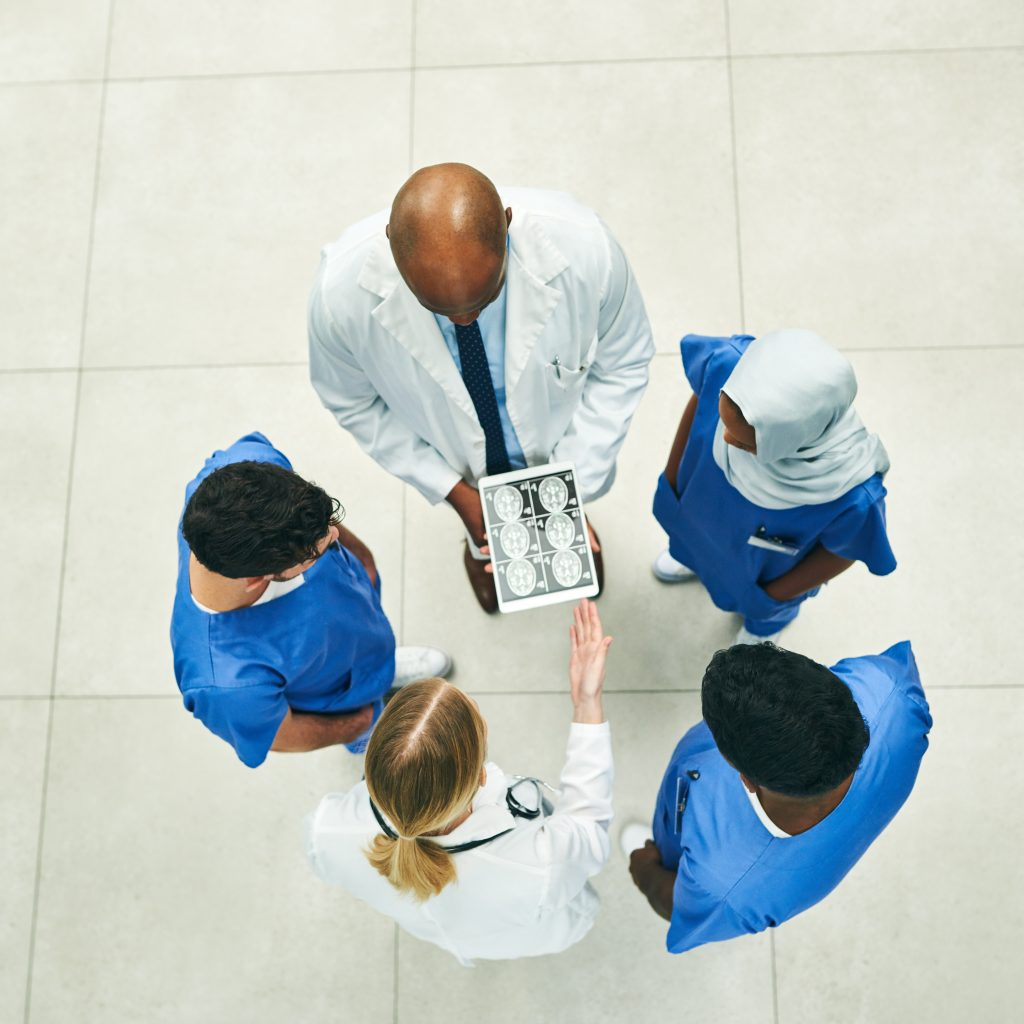 High angle shot of a team of doctors using a digital tablet to view scans in a hospital