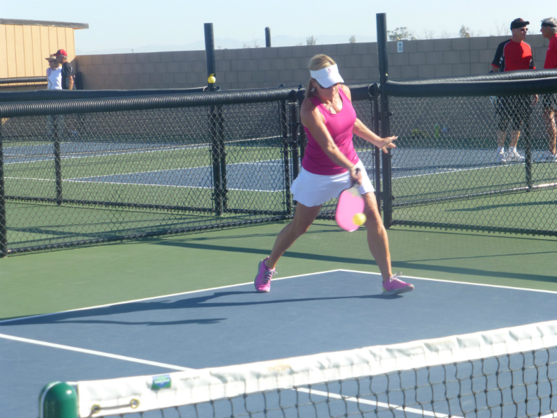 Suzanne driving the ball over the net