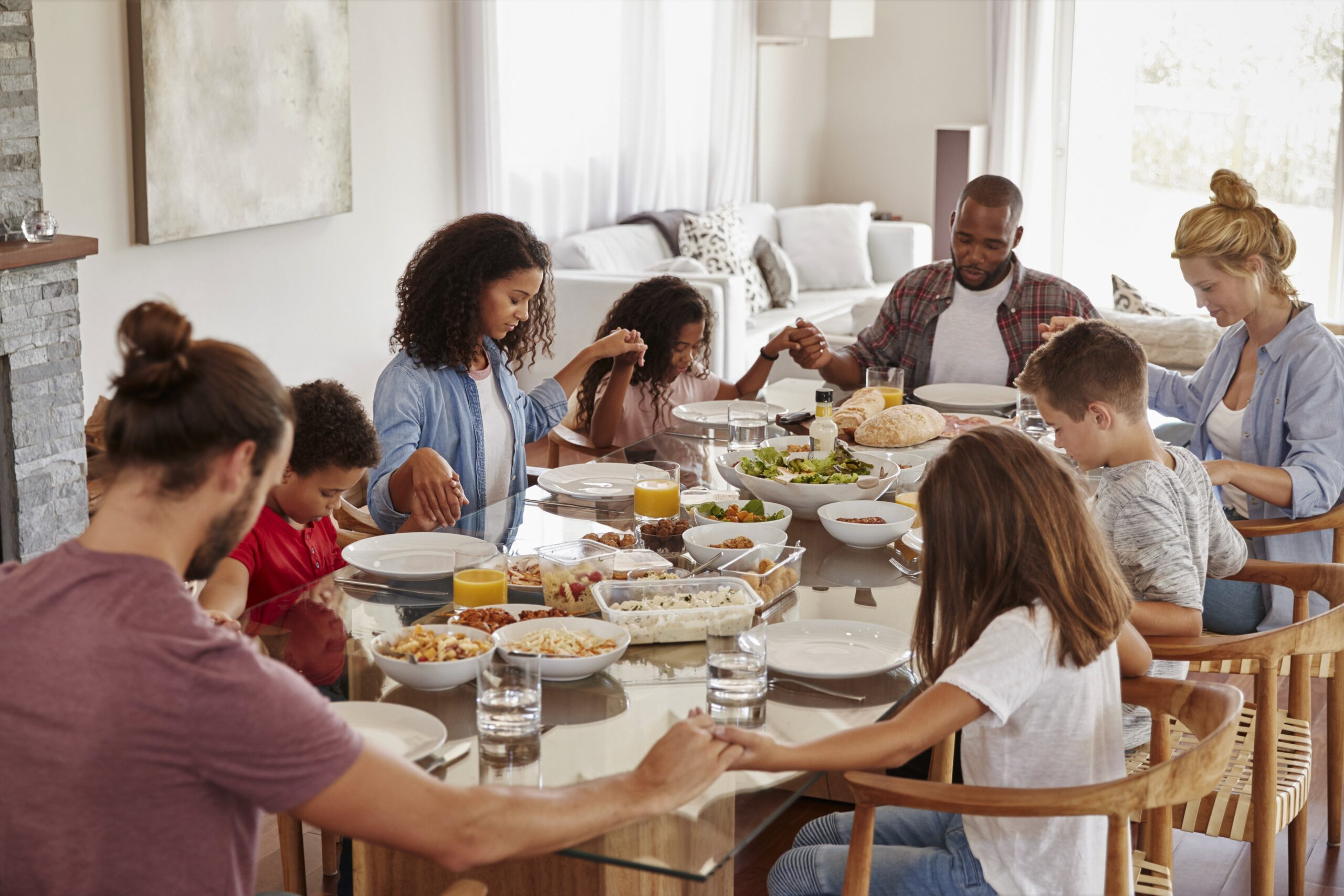 Family praying over Family Meal