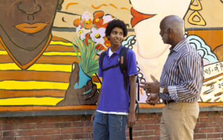 Adult male volunteer and teen against colorful mural