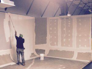 Man painting cyclorama wall