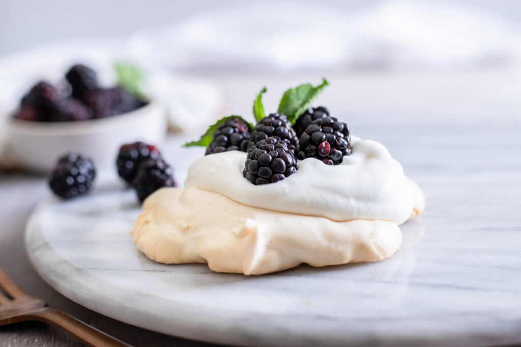 This mini blackberry pavlova recipes is the perfect summer dessert, crisp on the outside and marshmallow soft inside.  Top with your favorite whipped cream and fresh fruit for a show-stopping meringue dessert everyone will love.