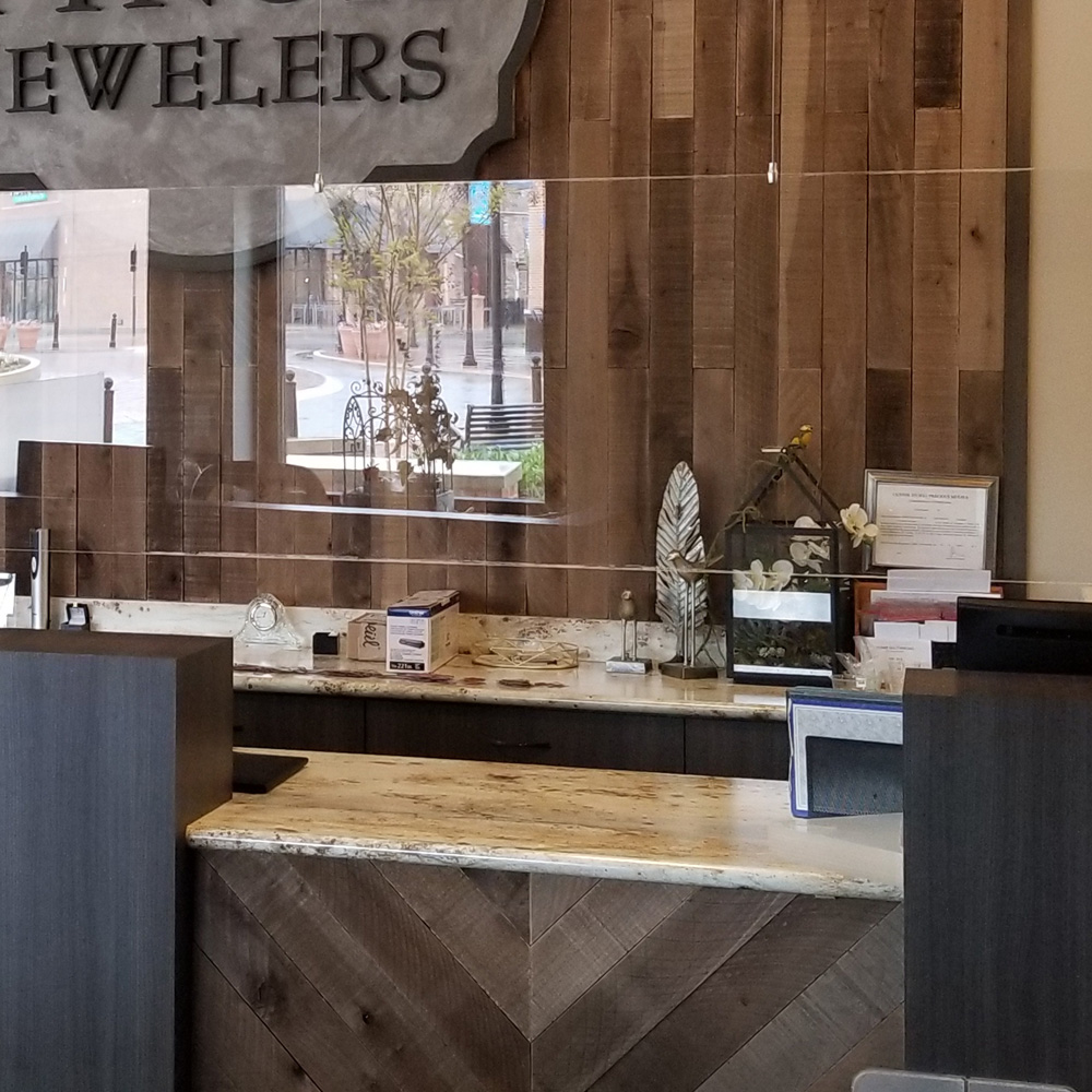 closeup photo of cable-suspended sneeze guards in retail jewelry store