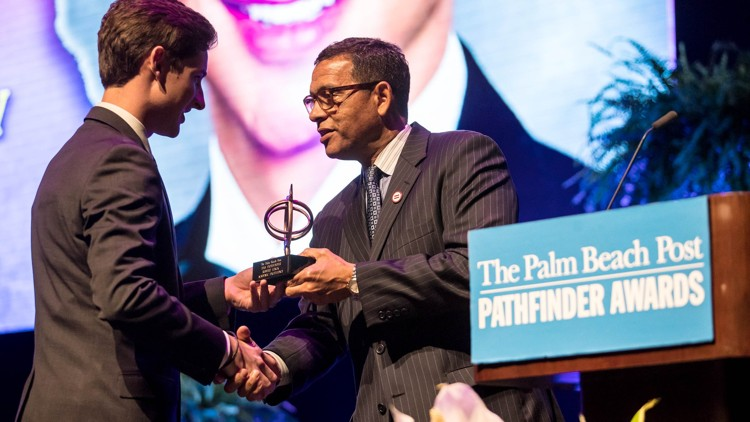 Robert Linck of Oxbridge Academy accepts the $4,000 scholarship for Academic Excellence from Patrick Franklin at the 35th annual Pathfinder Scholarship Awards. (Allen Eyestone / The Palm Beach Post)