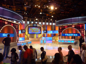 A staff member assists in directing the audience on the set of Family Feud. Image Credit: www.brianorndorf.com