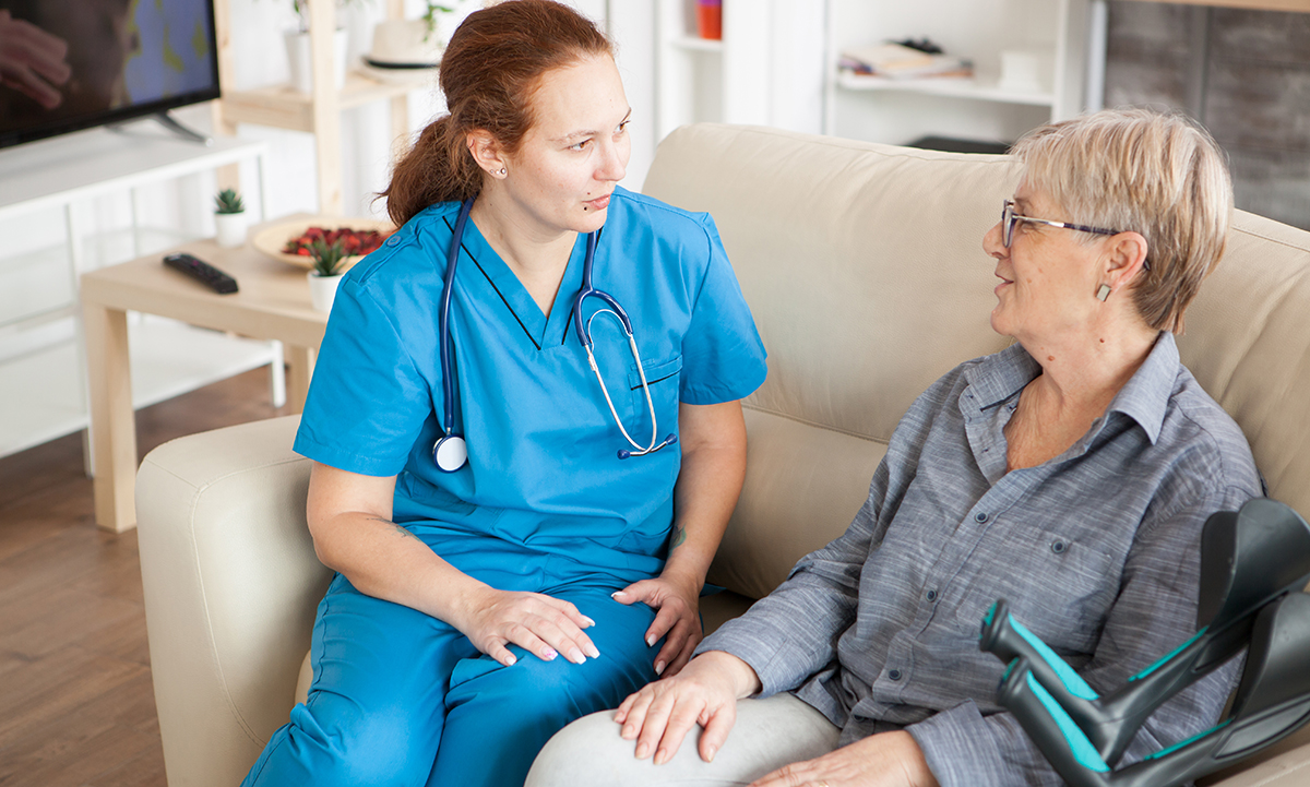 Home health care worker assisting woman at home.