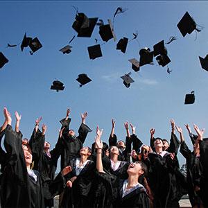 group of graduates throwing caps in air