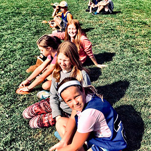 children sitting outside on grass