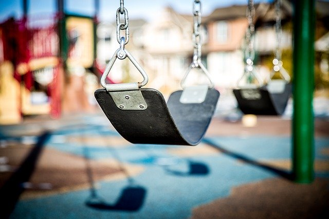 swing with playground equipment in background