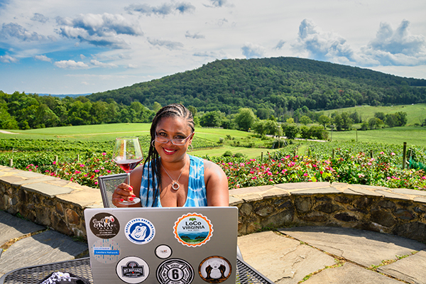 Woman sitting at a computer at a vineyard.