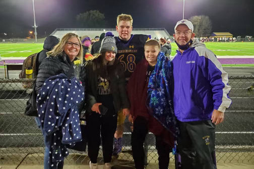 family with football player after a football game
