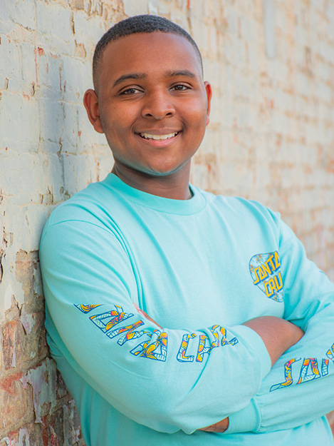 Young African American man in a blue standing against a white brick wall in a senior photo