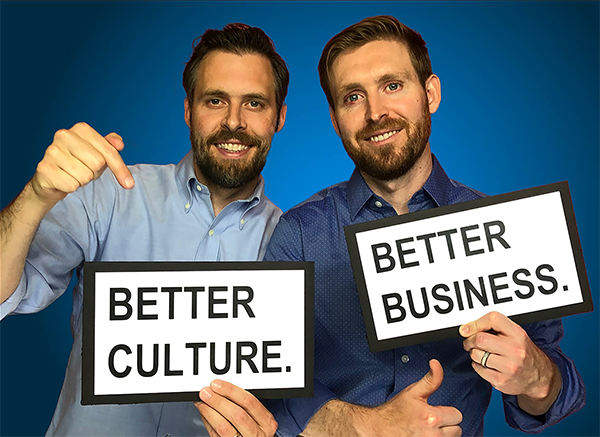 Two men with beards and blue shirts holding signs.