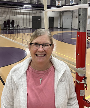 Woman smiling standing in front of a volleyball net wearing a pink shirt and white coat.