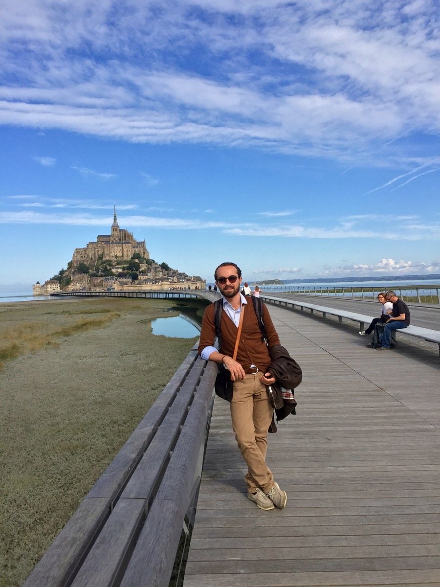 Cute French husband in front of Le Mont-Saint-Michel, a rocky island in Normandy, France.