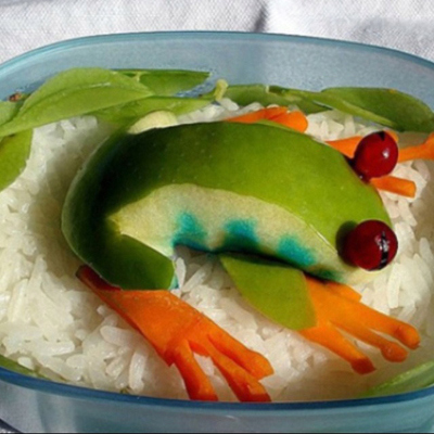 A creative kids plate with fruit and veggies arranged to look like a frog