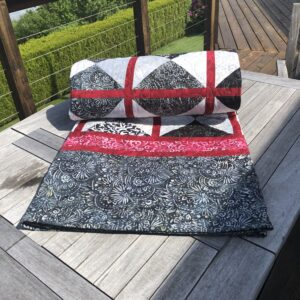 Quilt for sale rolled up on tabl;e