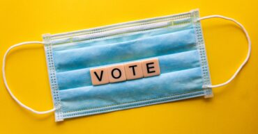 A face mask with the word VOTE in woodblocks on top