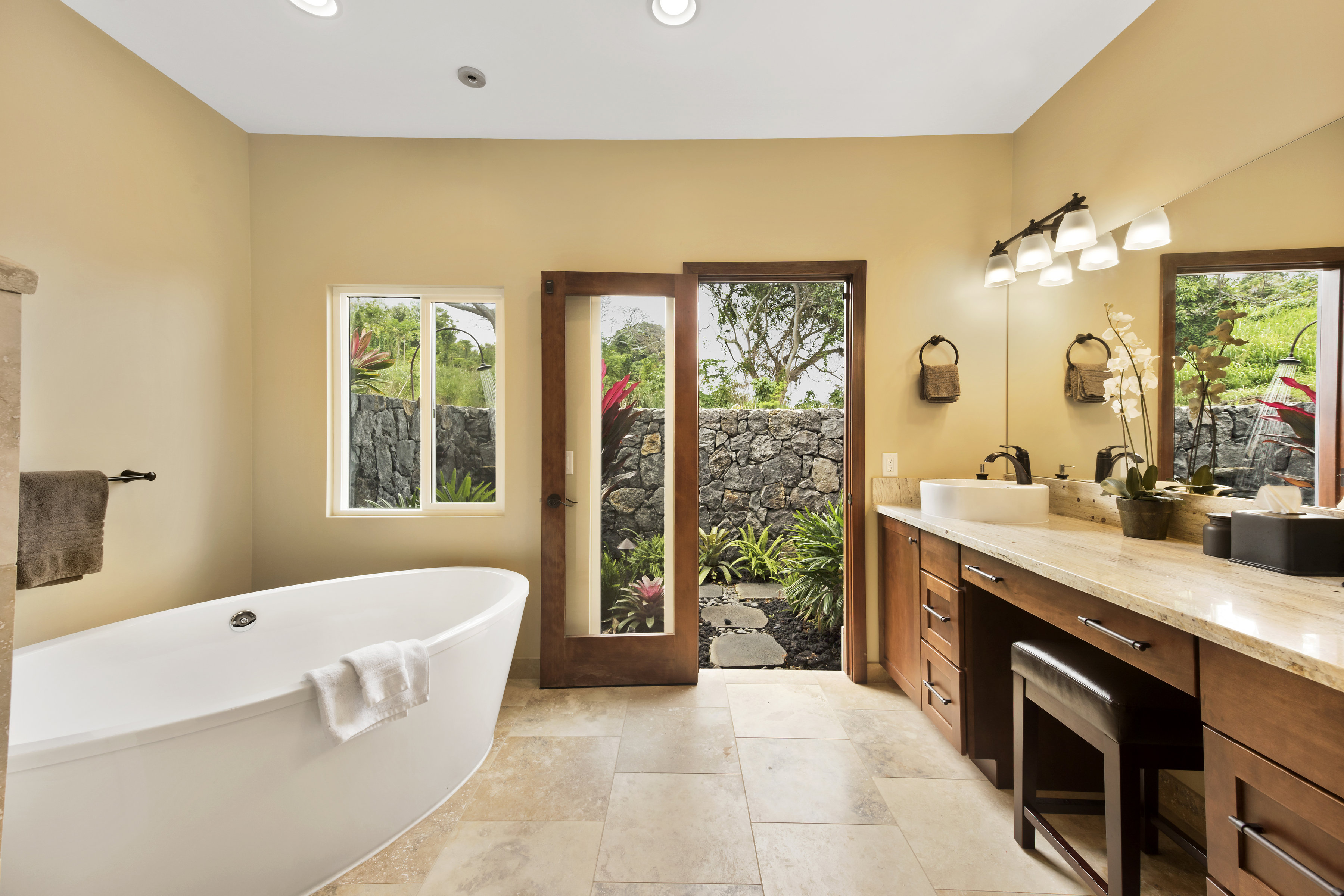 Master bathroom with rain shower head, outdoor shower and tub ceiling filler.
