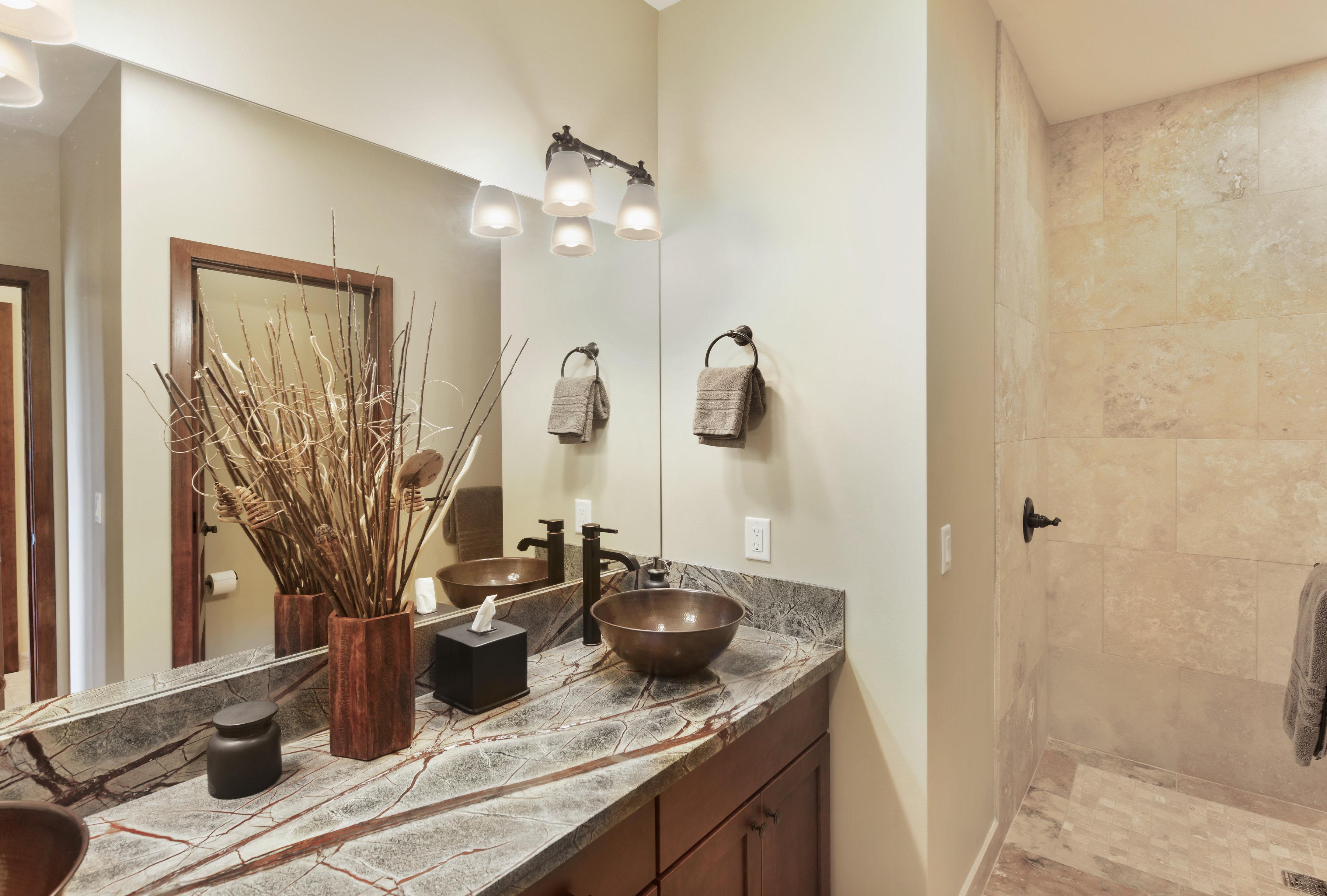 Queen bedroom bathroom with copper sinks.