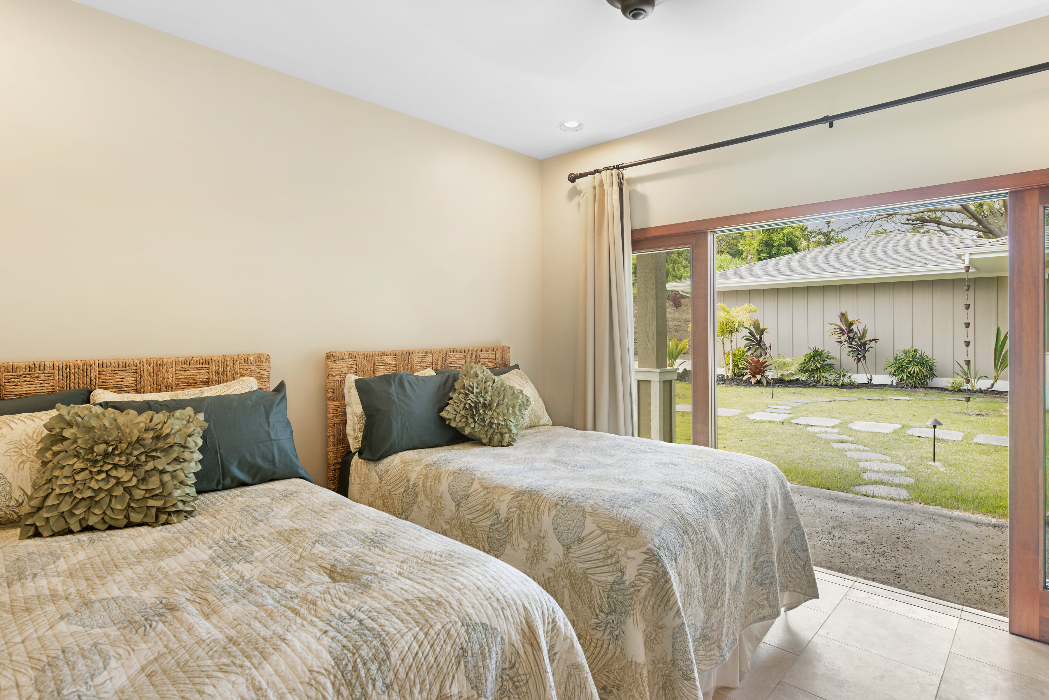 Bedroom 4 with two double beds and garden view.