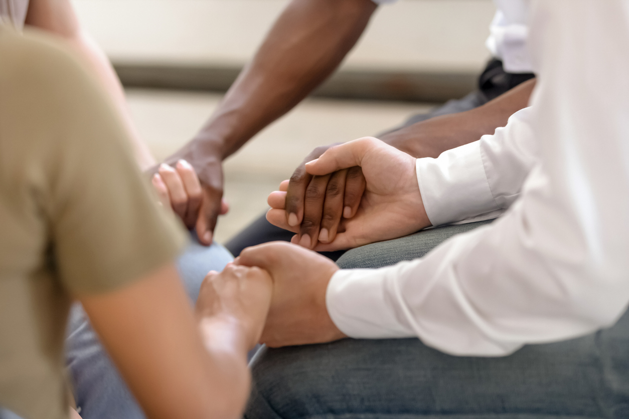 Close up of diverse religious people sit in circle hold hands pray together hope for help, multiracial men and women group