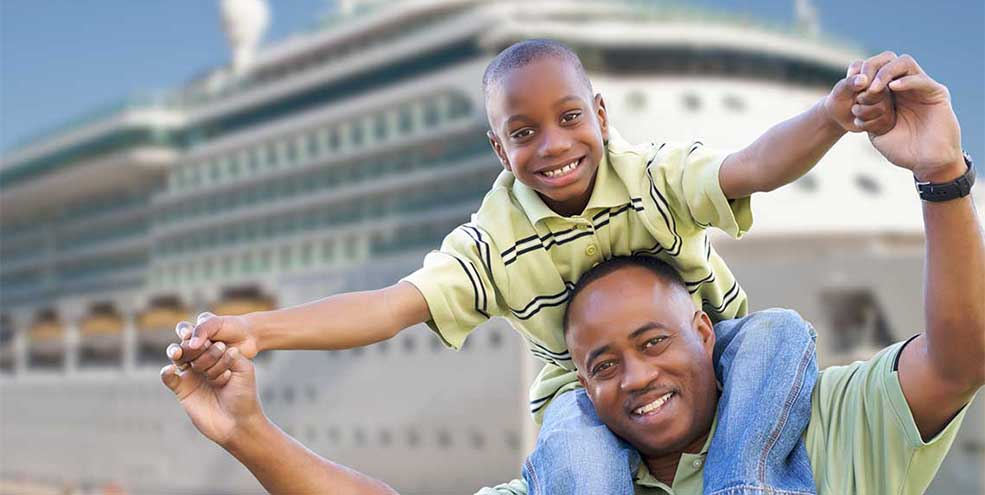 Father and son smiling in front of cruise ship