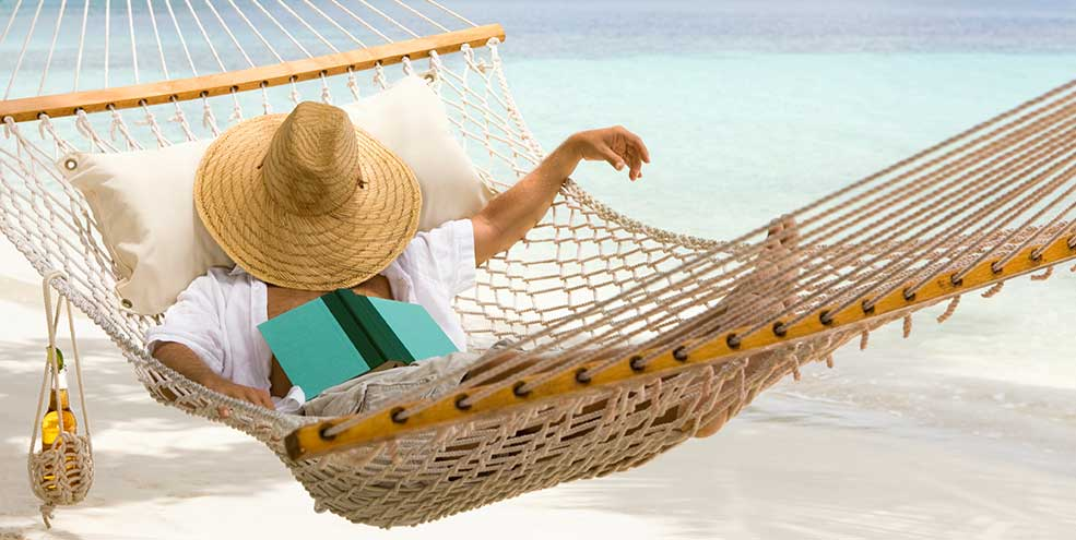 Man falling asleep while reading in a hammock on the beach