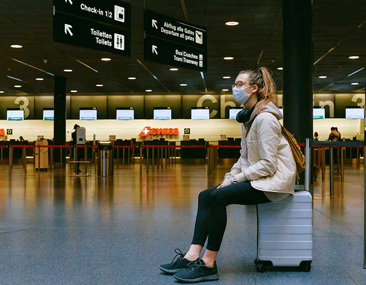 Young woman sitting on luggage wearing mask