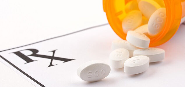 Prescription bottle open with pills spilling out on a RX form