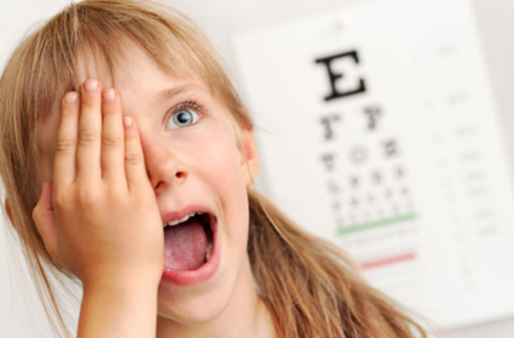 Child covering her eye to take a vision test