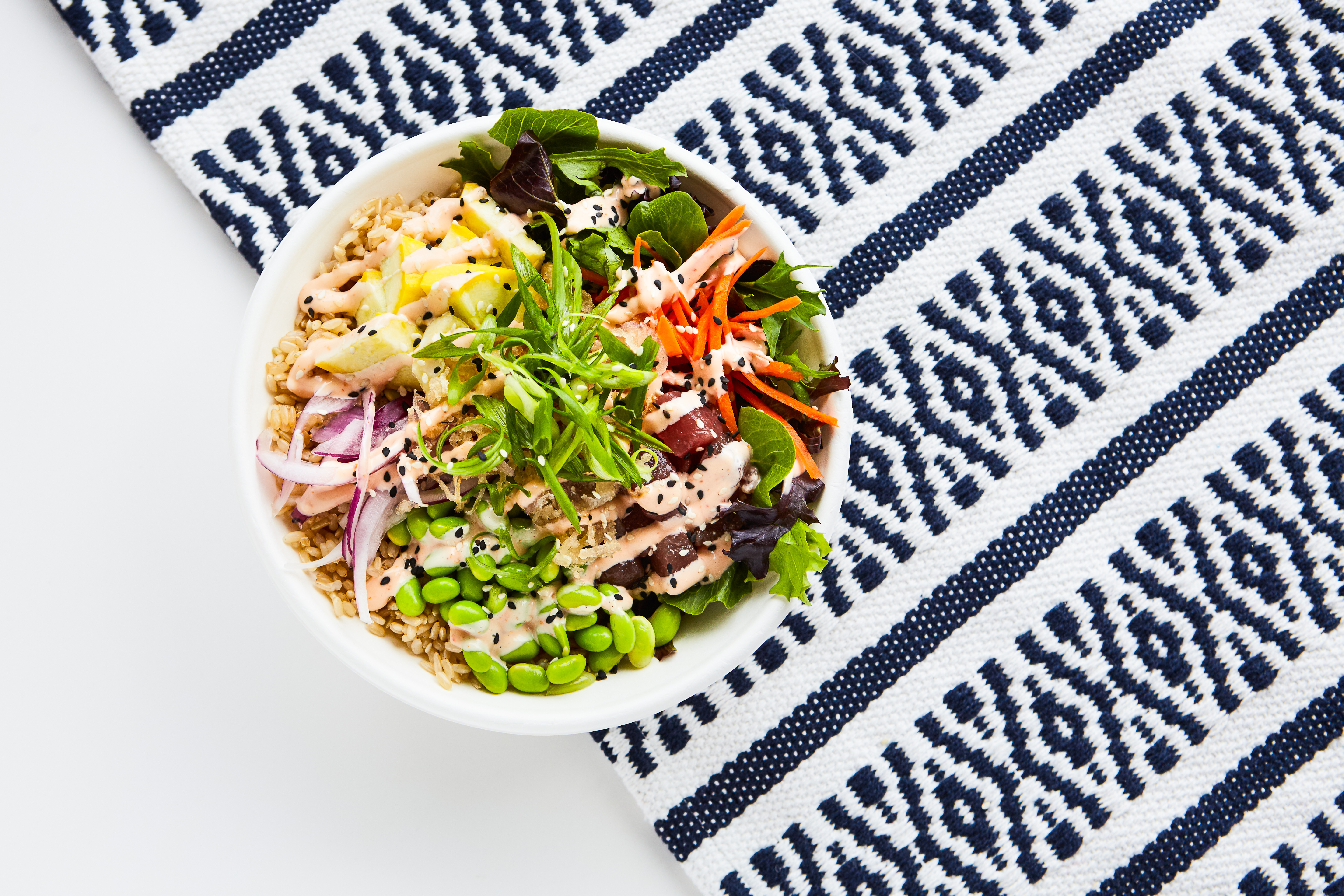 Poke bowls with fresh ingredients including tuna & chicken with fresh vegetables sauced up in BPI certified compostable bowls on a white table with a navy blue printed graphic runner.