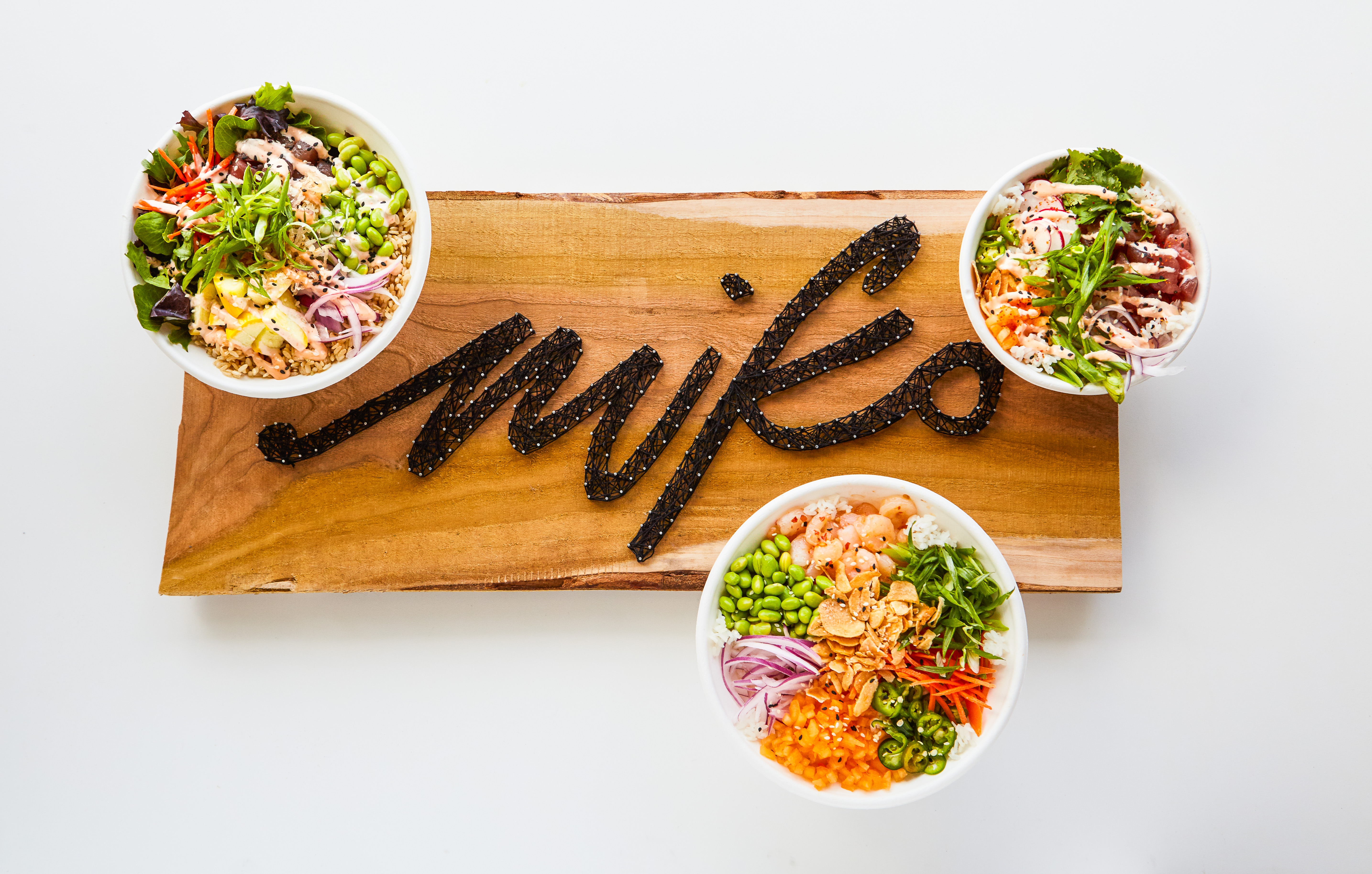 """Wood sign featuring string art that spells out """"Miko"""" with 3 bowls that feature vegetable, tuna and spicy chicken sitting around the edges in a graphic visual pattern."""