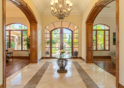 Entry with double glass doors and wood archways
