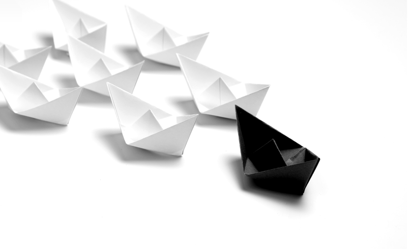 A black paper boat leads a flock of white paper boats (six firms)