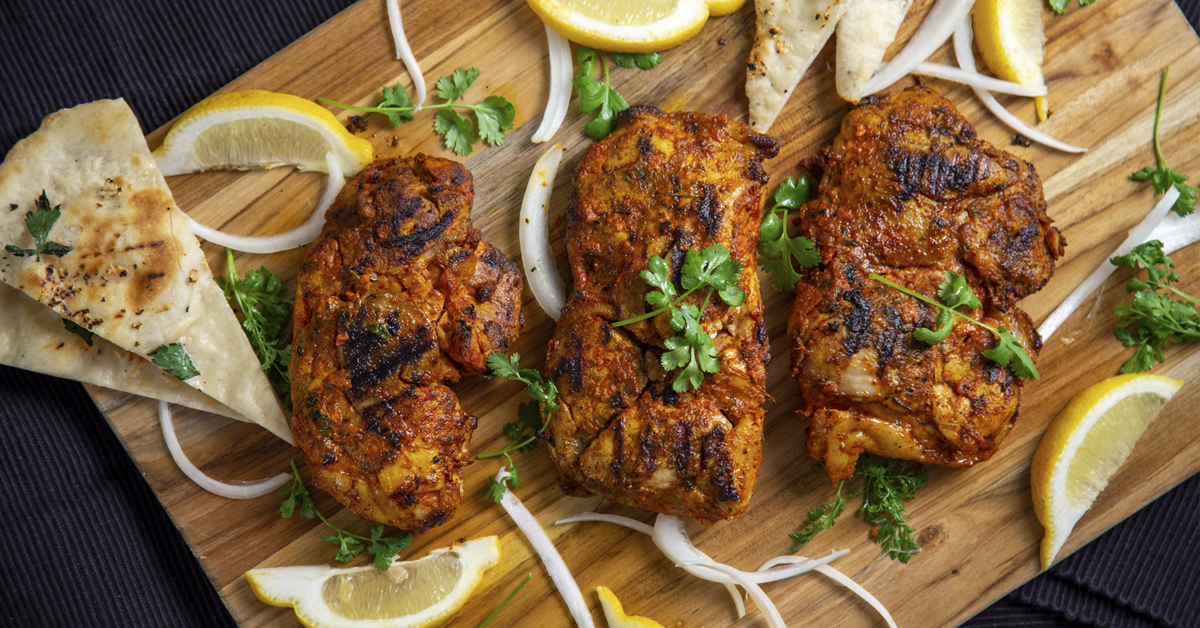 tandoori chicken on a chopboard garnished with lemon slices, onion, and coriander