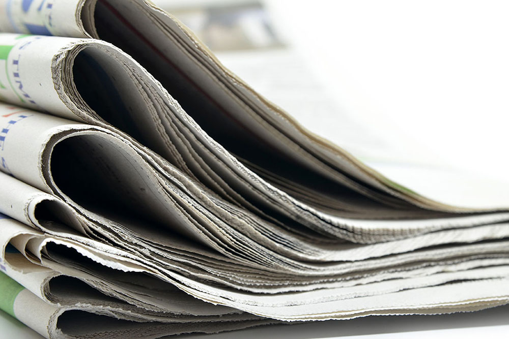 stack of newspapers used on the above the fold blog post